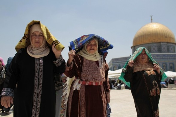 Palestinian women carry prayer mats in front of the Dome ...