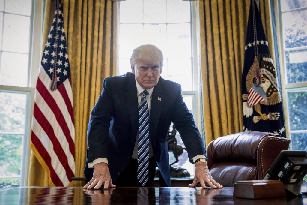 President Donald Trump poses for a portrait in the Oval ...