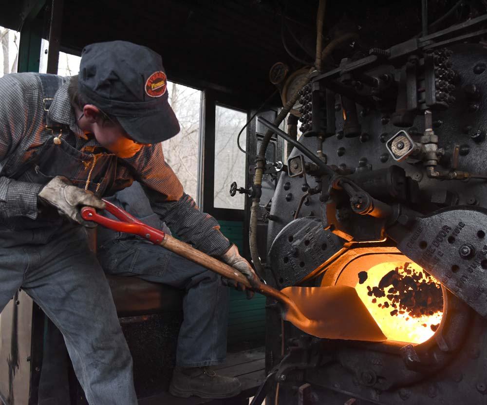 Man shovelling coal into a train engine