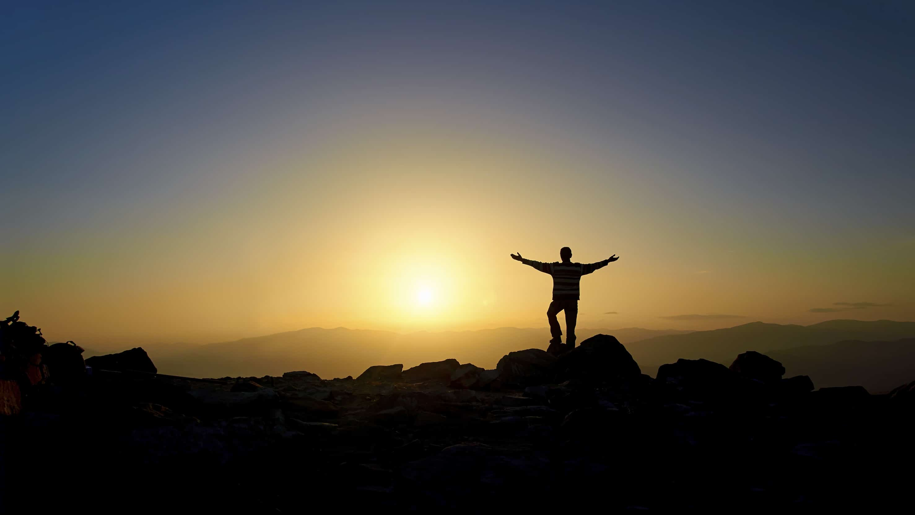 Man with arms outstretched standing on top of mountain ...